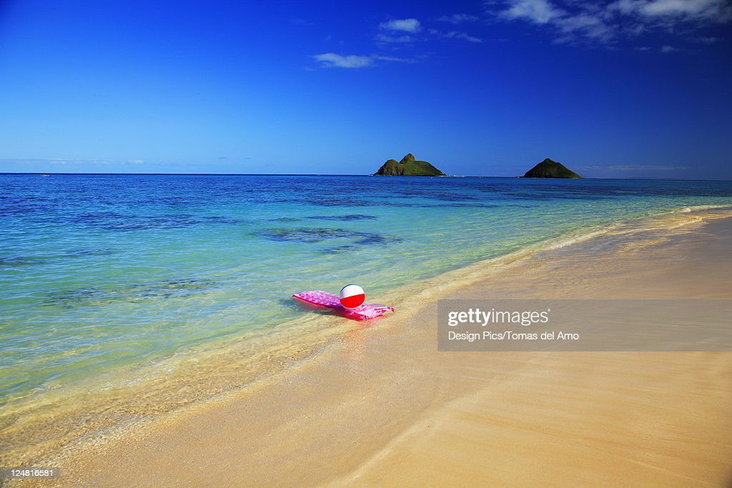 beach ball in ocean. Hawaii, Oahu, Lanikai, Pink Inflated Raft And Beachball On Clear Ocean Water, Beach Ball In