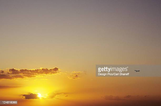 Hawaii, Sunball among clouds in dramatic yellow sunset sky, small airplane