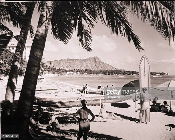 Waikiki Beach with vacationeers relaxing on the beach Diamond Head in backround Filed Jan1952