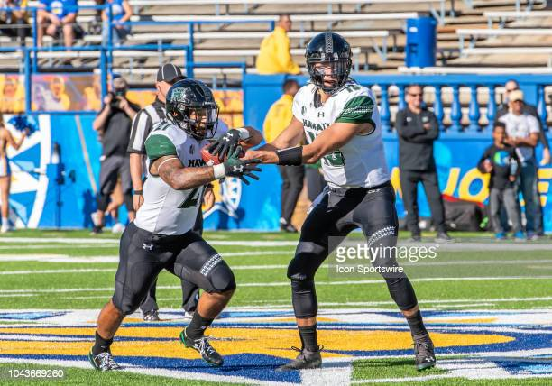 Hawaii Warriors quarterback Cole McDonald hands off the ball to Hawaii Warriors running back Fred Holly III during the game between the Hawaii...