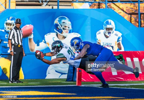 Hawaii Warriors running back Elijah Dale lunges into the end zone with San Jose State Spartans cornerback John Toussaint in pursuit for a touchdown...