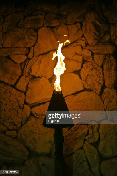 Hawaiian cone Tiki torch against stone wall in the night