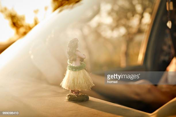 hawaiian dancer on dashboard of van during sunset - hula dancer stock pictures, royalty-free photos & images