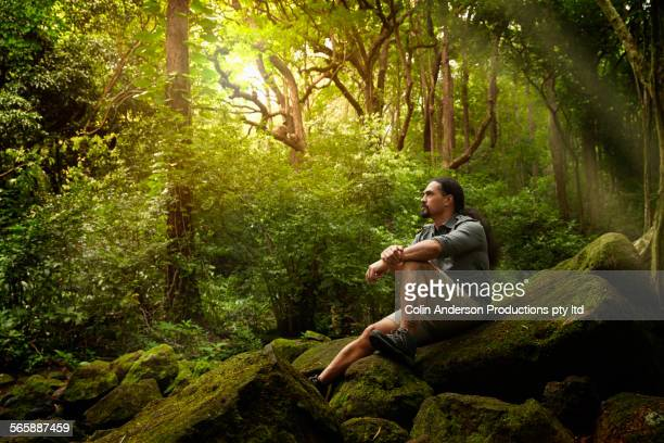 Hawaiian hiker sitting on boulder in forest