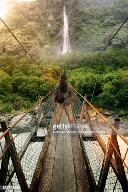hawaiian hiker standing on remote rope bridge - hawaiian waterfalls stock pictures, royalty-free photos & images