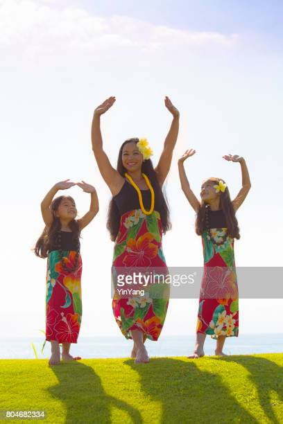 hawaiian hula dancer family with children dancing on grass lawn - hula dancer stock pictures, royalty-free photos & images