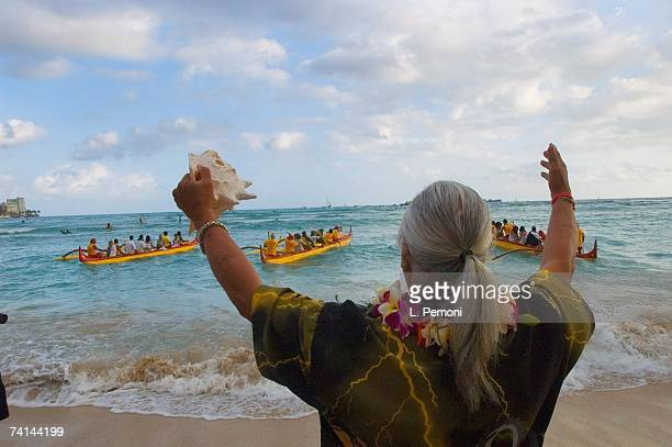A hawaiian kahu gives a blessing from the shore as canoes launch during the memorial service for singer Don Ho on May 5 2007 off of Waikiki Beach in...