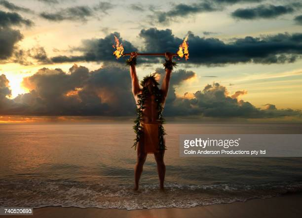 hawaiian man holding torches on beach - cerimônia - fotografias e filmes do acervo