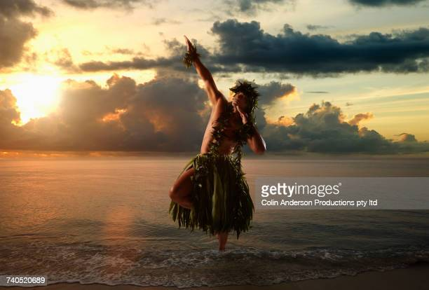 Hawaiian man hula dancing on beach