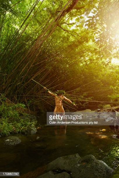 Hawaiian man in traditional outfit spear fishing
