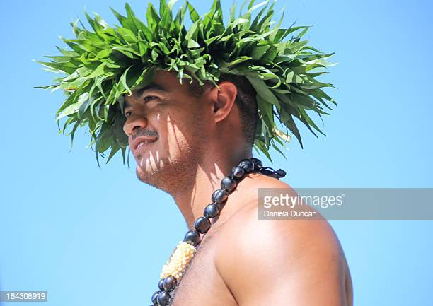 Hawaiian man representing Hawaiian culture and traditions, wearing a palm leaf headpiece and a Kukui Nut necklace at the Flower Parade in Oahu, which...