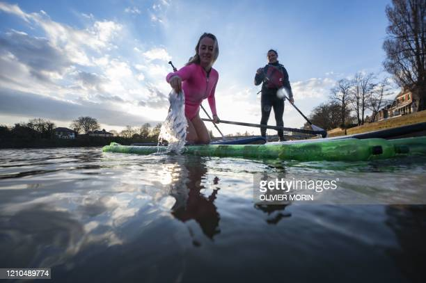 Hawaiian protest surfer Alison Teal collects trash while paddling on a stand up paddle made of used plastic bottles near Kew Bridge on the River...