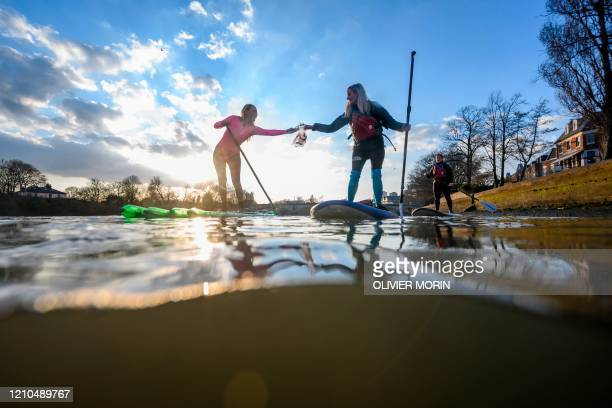 Hawaiian protest surfer Alison Teal collects trash while standing on a stand up paddle made of used plastic bottles on the River Thames near Kew...