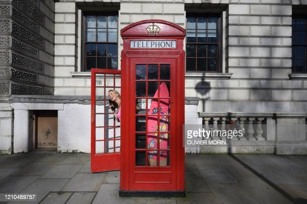Hawaiian protest surfer Alison Teal poses in a classic telephone booth with her surfboard during a visit to London on March 6 to raise awareness on...