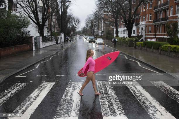 Hawaiian protest surfer Alison Teal recreates the famous Beatles Abbey Road album cover as she crosses Abbey Road during a visit to London on March 5...
