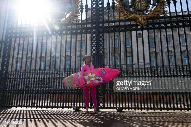 Hawaiian protest surfer Alison Teal stands at the main gate of Buckingham Palace with her surfboard during a visit to London on March 6 to raise...