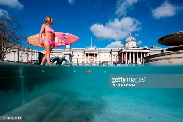 Hawaiian protest surfer Alison Teal walks in the Trafalgar Square fountain with her surfboard during a visit to London on March 6 to raise awareness...