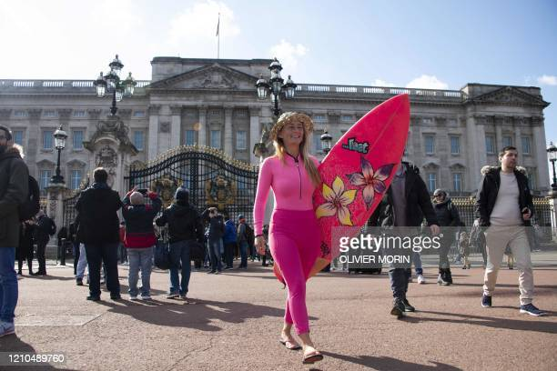 Hawaiian protest surfer Alison Teal walks outside Buckingham Palace with her surfboard during a visit to London on March 6 to raise awareness on the...