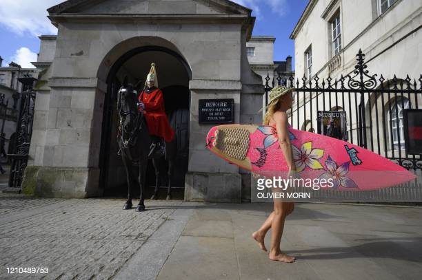 Hawaiian protest surfer Alison Teal walks past a Horse Guard during a visit to London on March 6 to raise awareness on the need to combat climate...
