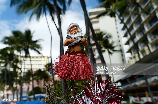 A Hawaiian Santa ornament sits atop a Christmas tree at Waikiki beach in Honolulu on December 25 2013 AFP PHOTO/Jewel SAMAD