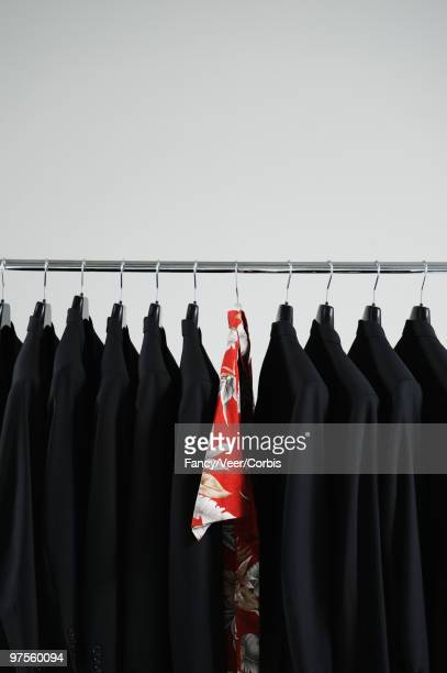 hawaiian shirt hanging between black blazers - mismatched clothes stock pictures, royalty-free photos & images
