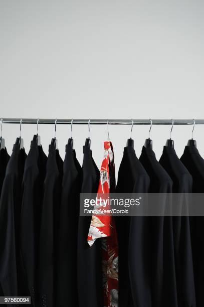 Hawaiian shirt hanging between black blazers