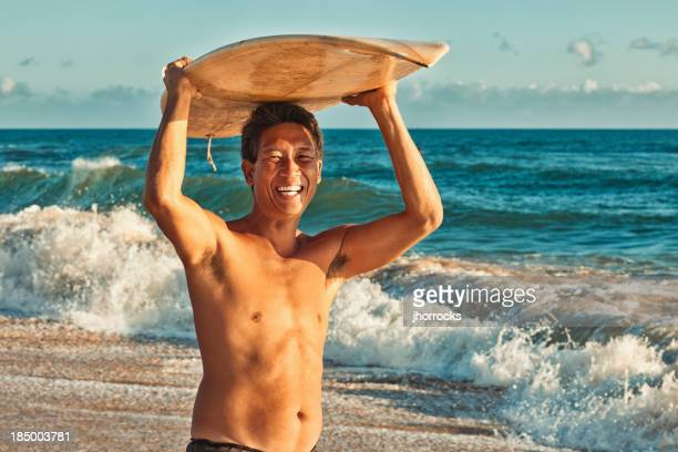 Hawaiian Surfer Standing on Beach with Surfboard