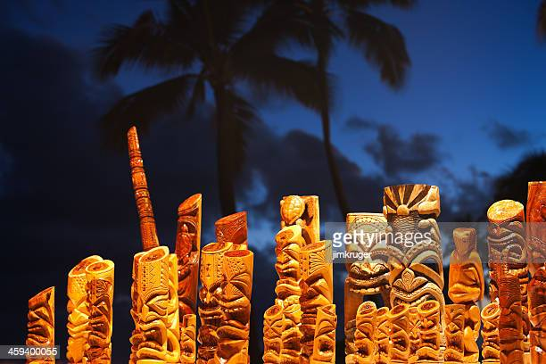 Hawaiian tiki mask art and blue palm tree sky.