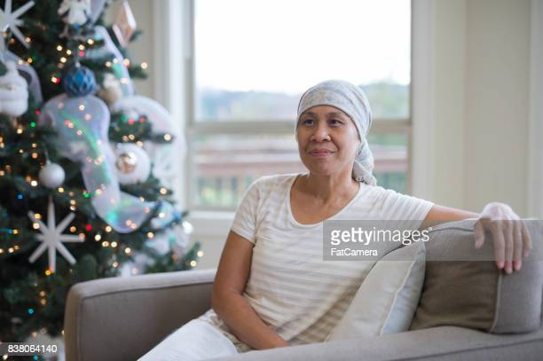 Hawaiian woman fighting cancer sitting on couch reading Bible