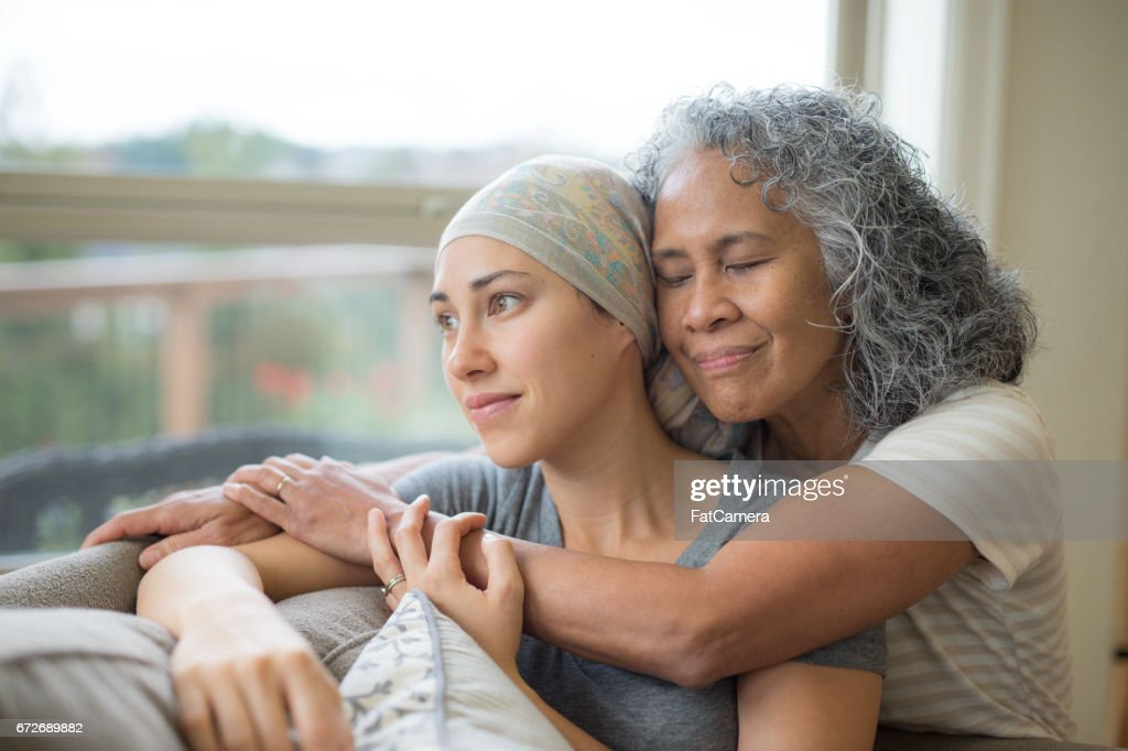 Hawaiian woman in 50s embracing her mid-20s daughter on couch who is fighting cancer : Stock Photo