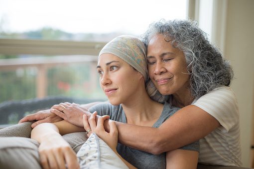 Hawaiian woman in 50s embracing her mid-20s daughter on couch who is fighting cancer 672689882