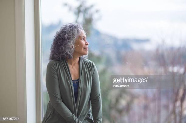 ハワイアンの女性彼女の窓際で静かに立っているし、熟考で外を見て