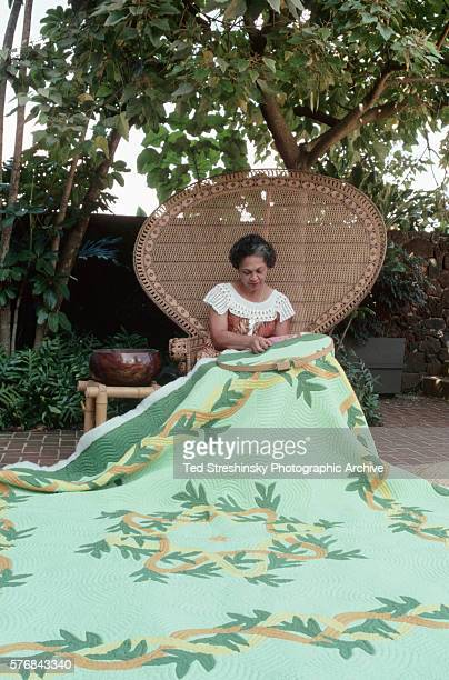 A Hawaiian woman stitches a green quilt with traditional plant motifs