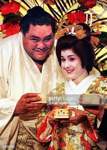 Hawaiianborn sumo grand champion Taro Akebono and his bride Christine Reiko Kalina raise wooden measures of sake during their wedding reception in...