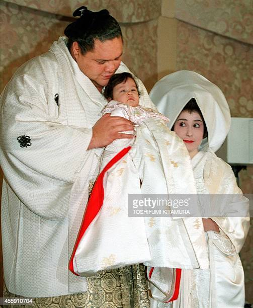 Hawaiiborn sumo wrestler Yokozuna Akebono amuses his 5monthold daughter Reina during a press conference prior to his wedding with Christine Reiko...