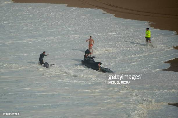 Hawaii's Garrett McNamara receives assistance at the Praia do Norte in Nazare on February 15 2020