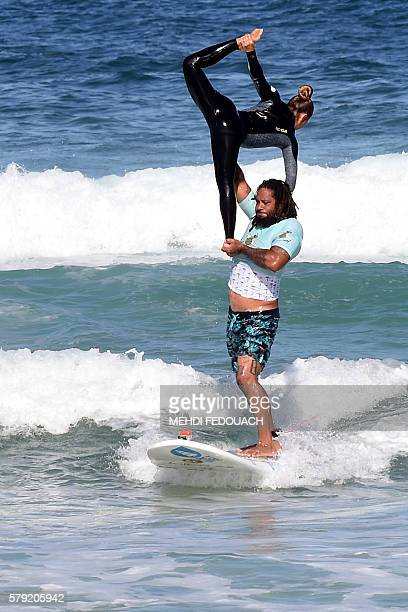 US Hawaii's Jordan Patterson and Angelee Homma compete in the International Tandem Surfing Championship on July 23 2016 in Biscarrosse / AFP / MEHDI...
