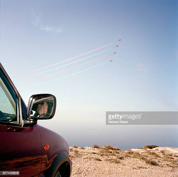 Hawk jets of the Red Arrows Britain's RAF aerobatic team practice display over a pilot officer who sits in his cool car on the cliff edge at RAF...