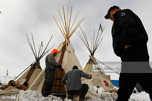 Hawk Laughing, left, of the Mohawk nation, and Jameson Dargen, middle work on building their teepee at Oceti Sakowin Camp on the edge of the Standing...