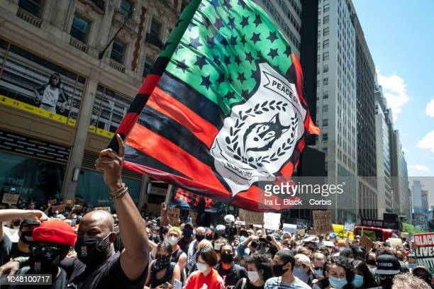 Hawk Newsome Chairperson of Black Lives Matter New York holds a flag with the words Peace Officer Black Opportunities on it before addressing the...