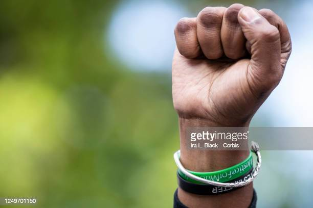 Hawk Newsome Chairperson of the Black Lives Matter Greater NY holds up a raised fist as he listens to Chivona Renee Newsome the CoFounder of Black...