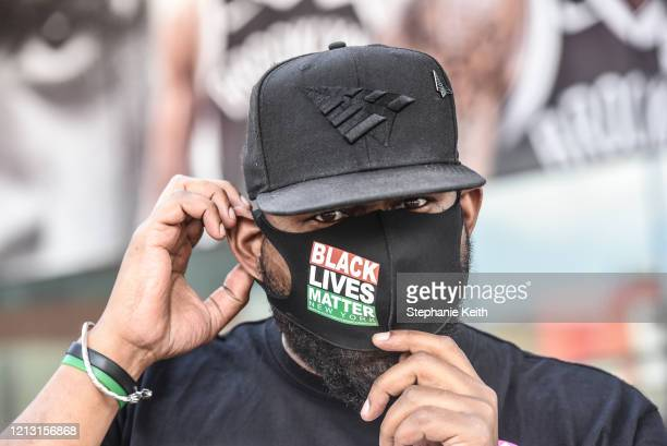 Hawk Newsome places a protective mask over his face before participating in a rally in front of the Barclays Center on May 15 2020 in the Brooklyn...