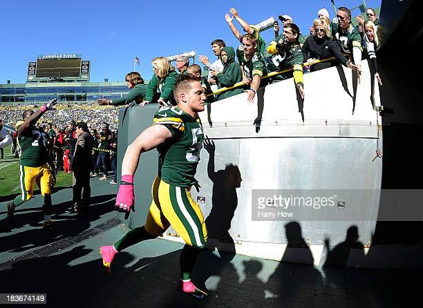 J Hawk of the Green Bay Packers celebrates a 229 win over the Detroit Lions with fans as he leaves the field at Lambeau Field on October 6 2013 in...