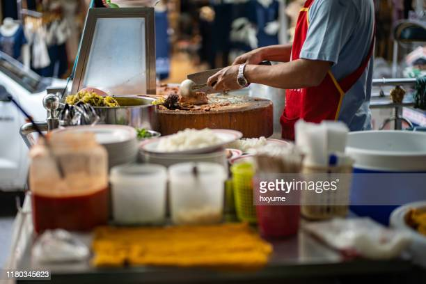hawker preparing thai style stewed pork leg meal on street - thai ethnicity stock pictures, royalty-free photos & images