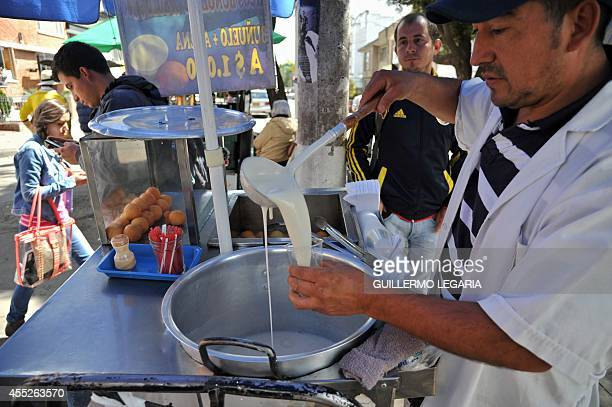 A hawker sells oat and fritters at his stall at a street of Bogota on September 5 2014 Many people start early in the morning to earn their living by...