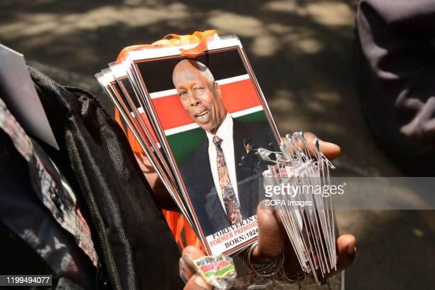 A hawker sells tags bearing portraits of the late former president of Kenya Daniel Arap Moi at Parliament building in Nairobi Kenya The former...