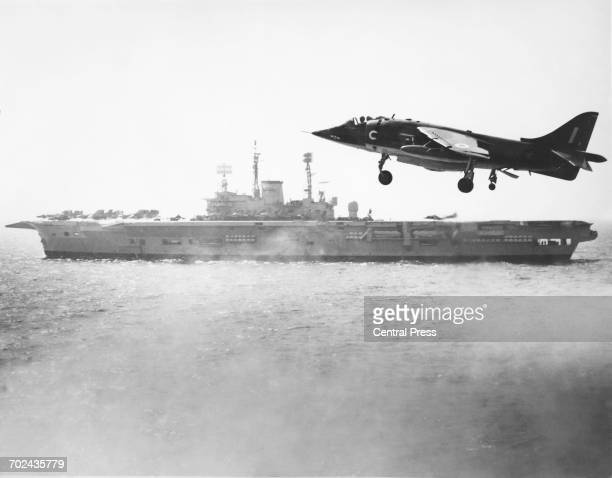 A Hawker Siddeley Harrier GR1 Vertical/Short Take Off and Landing jetpowered attack aircraft maneuvers to land aboard the Royal Navy Audaciousclass...