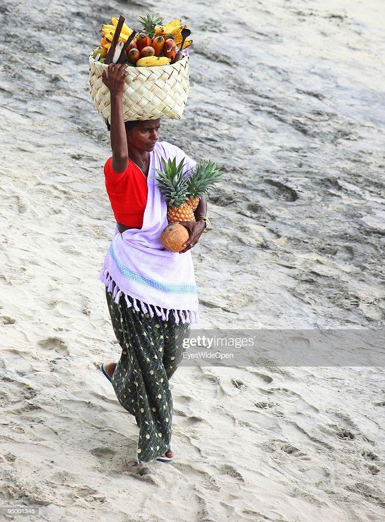 Hawker woman sells fruits like orange, banana, pineapple and papaya at the lighthouse beach of Kovalam on December 13, 2009 in Kovalam Beach near Trivandrum, India.