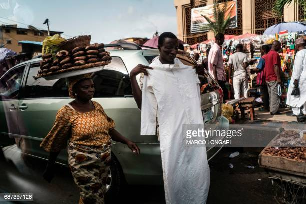 Hawkers sell food and clothes at the Balogun market in Lagos on May 23 2017 / AFP PHOTO / MARCO LONGARI