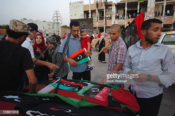 Hawkers sell rebel flags and posters in front of a former residence of Colonel Muammar Gaddafi as Libyan revolution tourists continue to celebrate...
